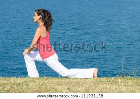 Woman exercising and stretching legs toward the sea on summer. Fitness beautiful caucasian model copy space. - stock photo