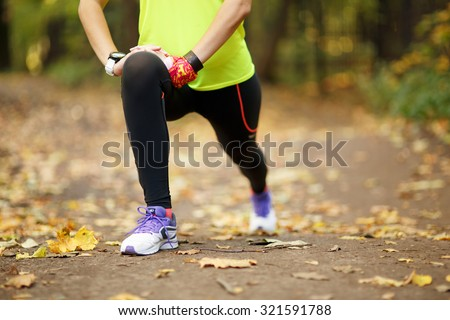 woman exercising and stretching muscles before sport activity in park