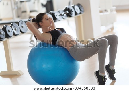 Woman exercising her abs on a Pilates ball. Natural light. Shallow DOF. - stock photo