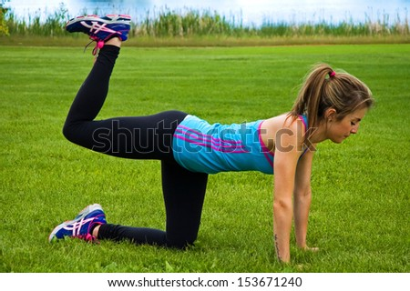 Woman exercising in a park, performing a yoga move.  This one is the bird dog.