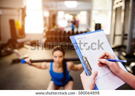 Woman exercising in gym, personal trainer, plan on clipboard - stock photo