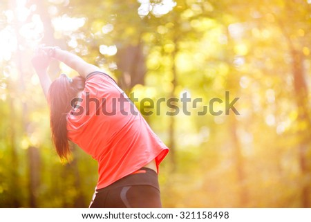 woman exercising in park, stretching hands up - stock photo