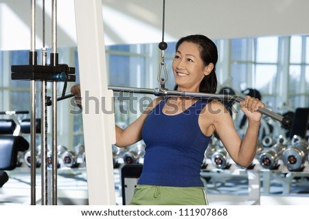 Woman exercising in the gym - stock photo