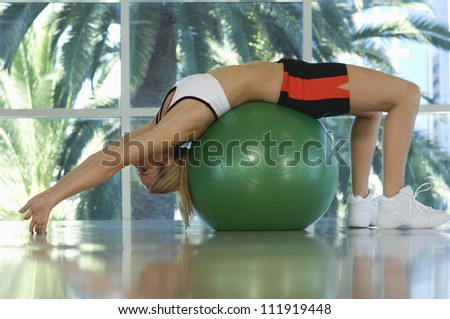 Woman exercising on a pilates ball - stock photo
