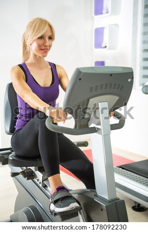 woman exercising on a stationary bike in gym. - stock photo