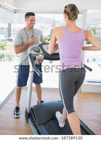 Woman exercising on treadmill and being timed by a personal trainer - stock photo