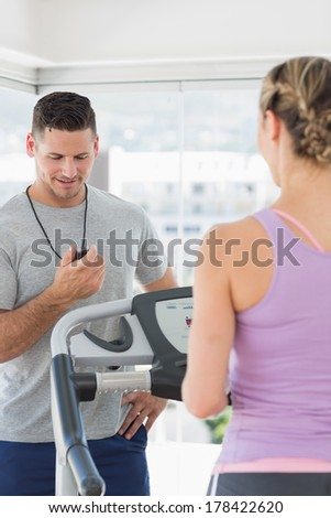 Woman exercising on treadmill and being timed by a personal trainer at gym - stock photo