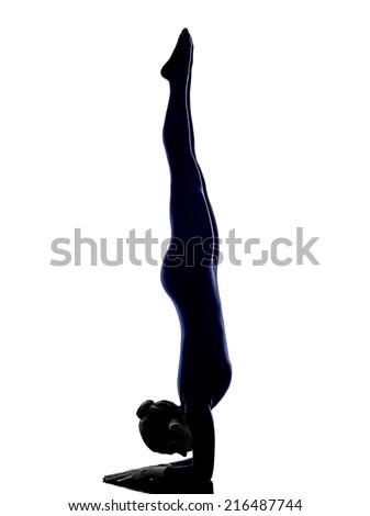 woman exercising vrschikasana scorpion pose yoga silhouette shadow white background - stock photo