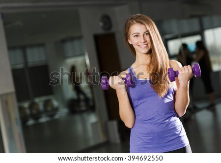 Woman exercising with dumbbells. Gorgeous brunette lifting some weights and working on her biceps in a gym. a young girl going sports