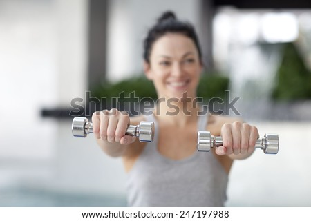 Woman Exercising With Dumbbells, Indoors  - stock photo