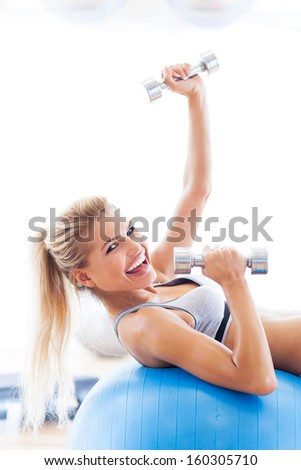 Woman exercising with dumbbells on a fitness ball  - stock photo