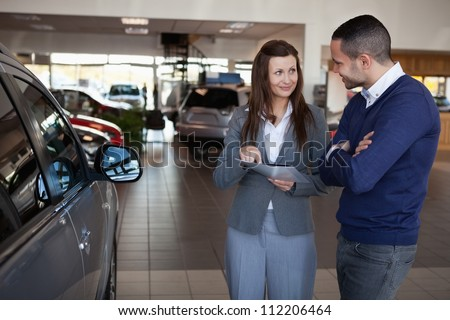 Woman explaining something to a man in a dealership - stock photo