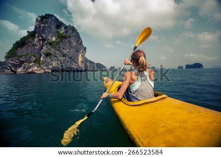Woman exploring calm tropical bay with limestone mountains by kayak. Ha Long Bay, Vietnam - stock photo