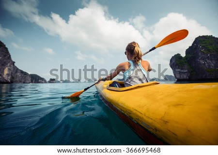Woman exploring calm tropical bay with limestone mountains by kayak. Ha Long Bay, Vietnam - stock photo