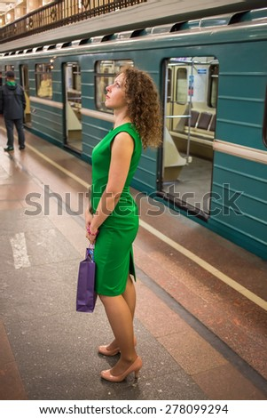 woman exploring information board in the subway - stock photo