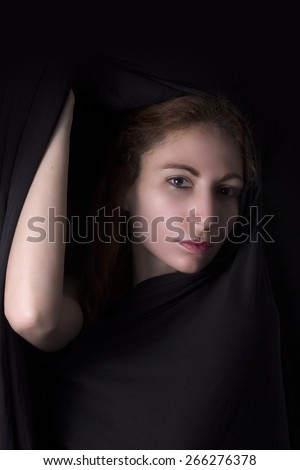 Woman face and elbow hand appear from black dark background - Beauty portrait  - stock photo