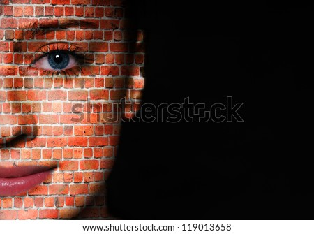 Woman face covered with brick wall pattern over black background - stock photo