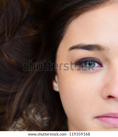 Woman face lying on autumn leaves - stock photo