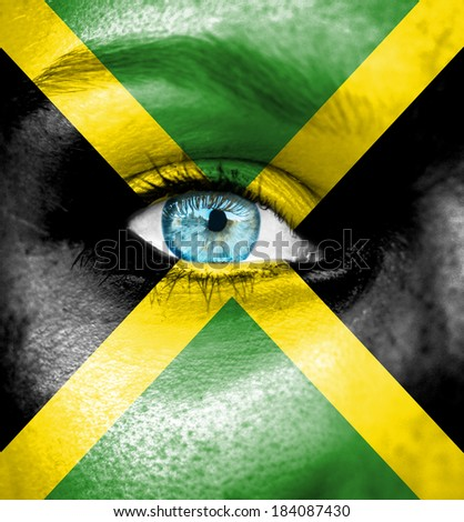 Woman face painted with flag of Jamaica - stock photo