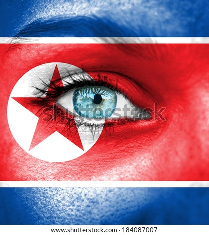 Woman face painted with flag of North Korea
