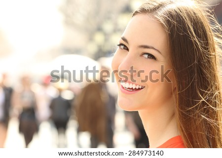 Woman face smile with perfect teeth and smooth skin looking you on the street - stock photo