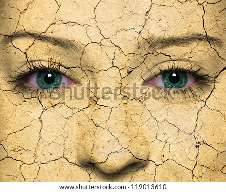 Woman face with cracked earth pattern - stock photo