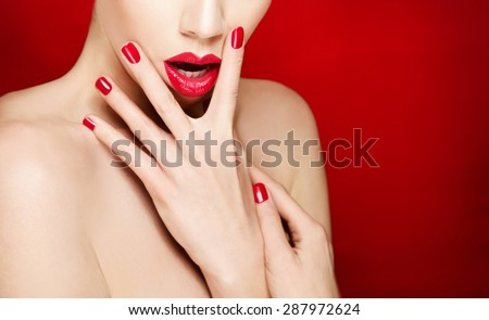 Woman face with red lips and red manicured nails. isolated on red background - stock photo