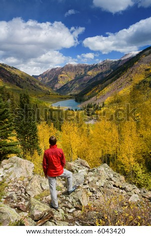 Woman facing away from camera looking over a beautiful autumn landscape in Colorado.