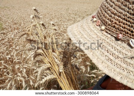 woman farmer with hat in a wheat field - stock photo