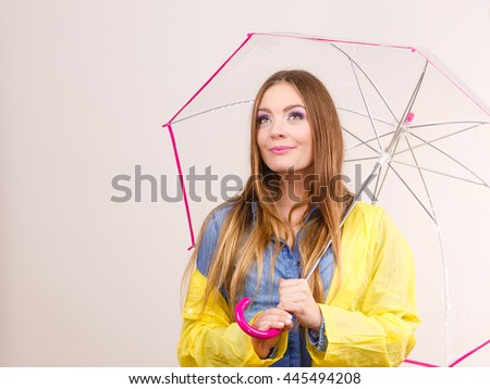 Woman fashionable rainy girl wearing waterproof yellow coat holding transparent umbrella. Meteorology, forecasting and weather season concept