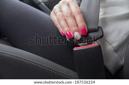 Woman fastening seat belt in car - stock photo