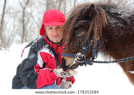 woman feeding hors outdoors, side view - stock photo