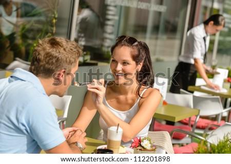 Woman feeding man cheesecake at cafe couple flirting romantic happy - stock photo