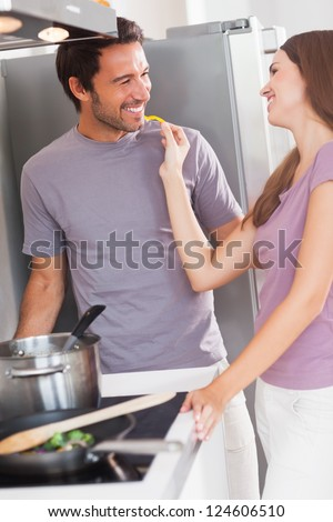 Woman feeding man with a yellow pepper in kitchen at the stove