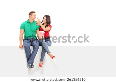 Woman feeding popcorn to her boyfriend seated on a panel isolated on white background - stock photo