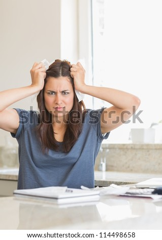 Woman feeling angry about bills in kitchen - stock photo