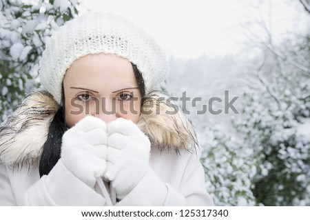woman feeling cold in snow covered landscape - stock photo