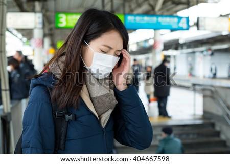 Woman feeling dizzy at train platform - stock photo