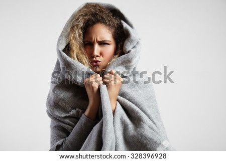 woman feeling freeze and wrap up in a blanket - stock photo