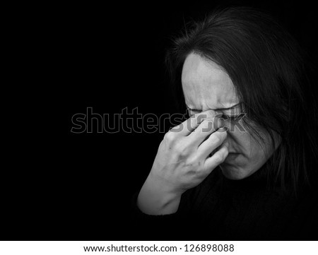 woman feeling pain, frowning with hand on head with black background - stock photo