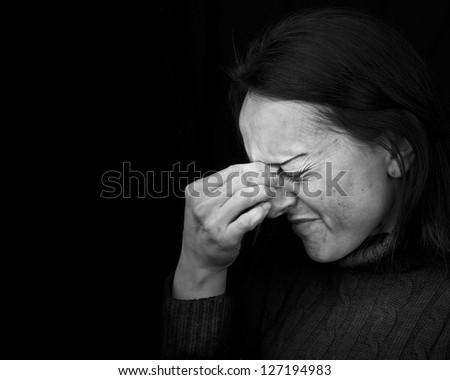 woman feeling pain, frowning with hand on head with black background and copy space