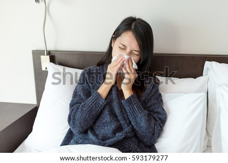 Woman feeling sick and sneeze on bed