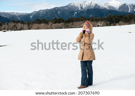 Woman feeling warm in the snow - stock photo