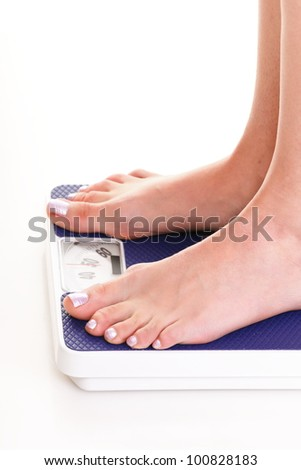 Woman feet and blue weight scale isolated on white background