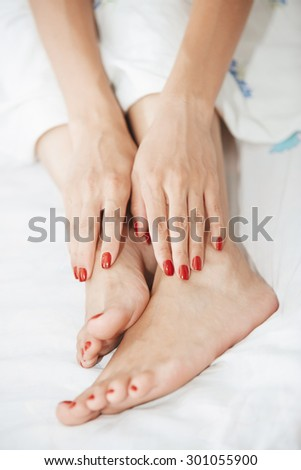 Woman feet and hands with red nail polish - stock photo
