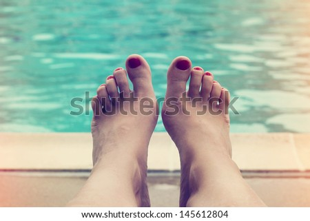 Woman feet closeup of girl relaxing on beach on sunbed. - stock photo