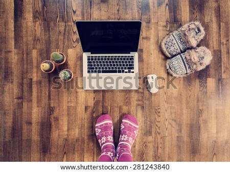 Woman feet in warm socks standing on a wooden floor with a laptop in winter. Online work concept - stock photo