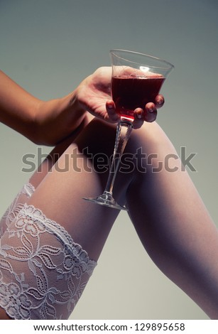 woman feet in white stockings and hand with wineglass on gray background