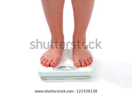 Woman feet on a scale as she checks her weight. - stock photo