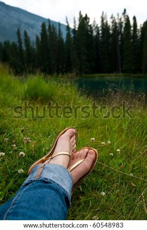 woman feet on grass near a lake - stock photo